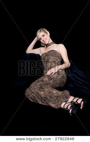 Beautiful young blond woman in an animal print evening gown sitting against a black covered hassock and background