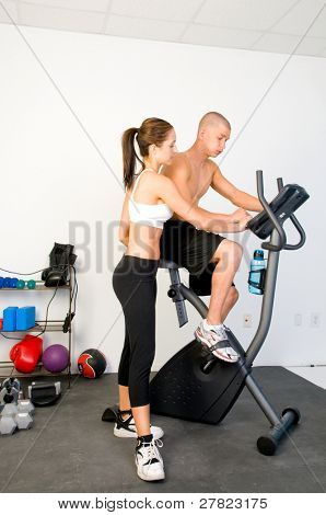 Young man training in the gym with his personal trainer and  riding a stationary bike while a female trainer stands by