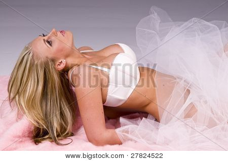 Beautiful large busted young fashion model with long blond hair in white and pink lingerie laying down and wrapped in white tool