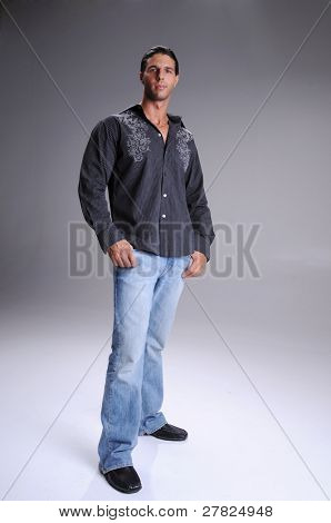 Muscular young man standing in jeans and a black long sleeve dress shirt neck tee shirt