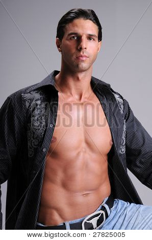 Muscular young man kneeling in jeans and an unbuttoned black long sleeve dress shirt neck tee shirt