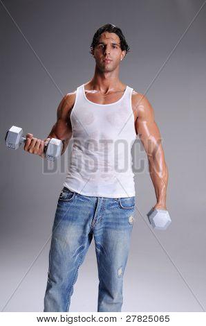 Hombre joven en pantalones vaqueros y una camiseta blanca esposa batidor elaboración de levantamiento de pesas