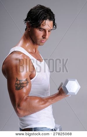 Muscular young man standing in jeans and a white wife beater tee shirt working out lifting weights