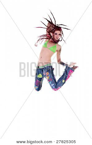 Heavily tattooed young hippie woman in retro patchwork jeans and bikini top with long red dreadlocks dancing and jumping in the air