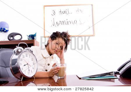 Young professional business woman struggling with working in an office early in the AM