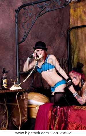 Rabble rousing pair of burlesque dolls dancers gathered on the bed of their dressing room