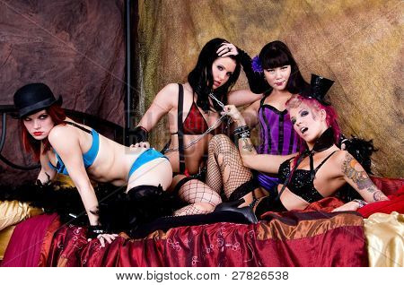 Rabble rousing group of burlesque dolls dancers gathered on the bed of their dressing room