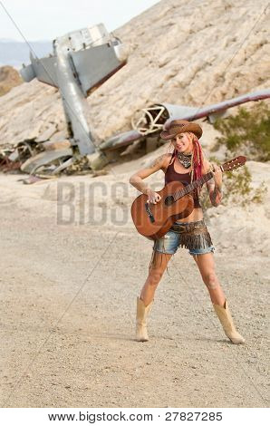 young alternative country girl standing outside in front of a plane crash and playing guitar