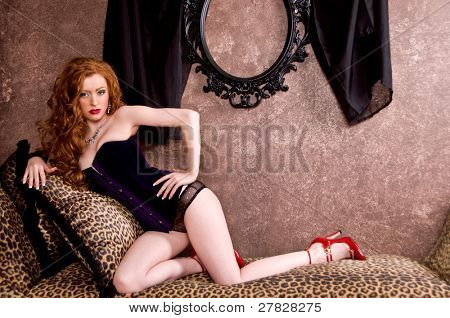 Beautiful redheaded model in purple velvet corset