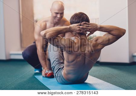 poster of A Man Performs A Physical Exercise On The Crunches. Individual Training In A Fitness Club With A Tra