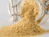 Nutritional Yeast Background. Nutritional Inactive Yeast Spilled From Glass Jar On White Background. poster