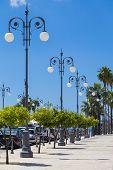Wrought Lanterns On The Larnaca Seafront, Cyprus. Larnaca City. Modern Street On Blue Cloudy Sky Bac poster