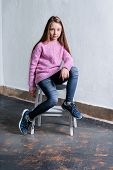 Confident Child Girl Sitting Fashion Pose On Chair, Concrete White Background. Stylish Model In Pink poster