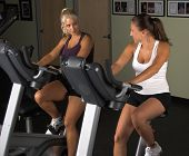 image of exercise bike  - Two women during a cardio workout on an exercise bikes in the gym - JPG