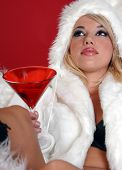 Sexy blond snow bunny in a white furry coat and hat and black hot pants over a red background reclined with a martini poster