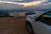 White Suv Car At Cliff Sunrise Over Lake On Background. Road Trip poster