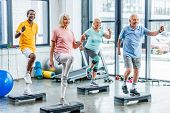 Smiling Multiethnic Senior Athletes Synchronous Exercising On Step Platforms At Gym poster