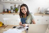 Happy Attractive Young Woman Sitting At Kitchen Table Working Through Papers, Calculating Home Budge poster