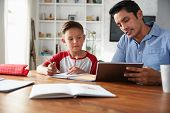 Hispanic pre-teen boy sitting at table working with his home school tutor, using tablet computer poster