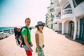 Family Walking Along The Waterfront Street. A Man, Woman And Child Walk Along The Seashore. Vacation poster