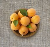 Top View. Ripe Apricots On Rustic Background. Bowl With Apricots With Leaves. Ripe Apricots With Cop poster