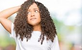 Young beautiful woman with curly hair wearing white t-shirt confuse and wonder about question. Uncer poster