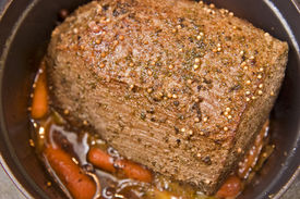 stock photo of pot roast  - Beef roast and carrots simmering slowly on the stove - JPG