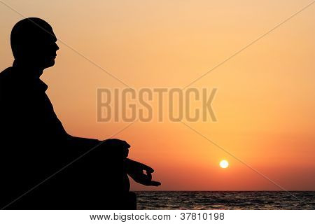 A Young Man Sitting In Lotus Position And Meditating On A Beach In The Evening With Sun Setting In T