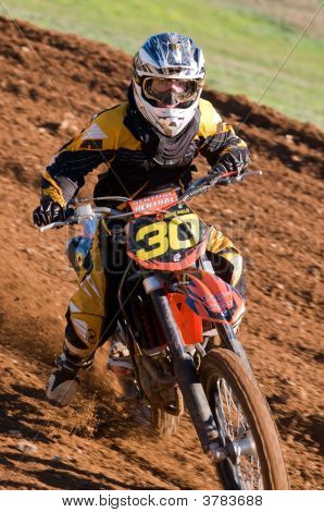 Motocross Rider Cornering Looking Straight At The Camera
