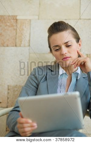 Thoughtful Business Woman Looking In Tablet Pc