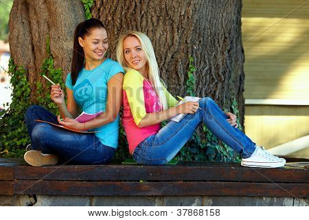 Two Beautiful Smiling Students Study On Bench Under An Old Oak Tree