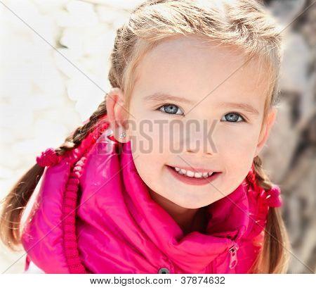 Outdoor Portrait  Of Cute Sitting Little Girl