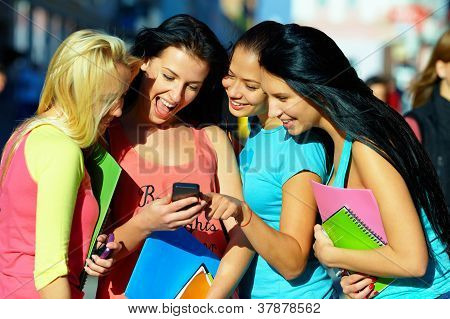 Grupo de estudantes do sexo feminino bate-papo em rede Social no celular