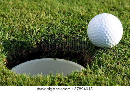 A Golf Ball Sits At The Lip Of The Hole