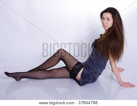 Beautiful Girl Lying On A Reflective Surface On The White Background