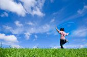 stock photo of jump rope  - Young girl skipping on the green grass in the beautiful blue sky background - JPG