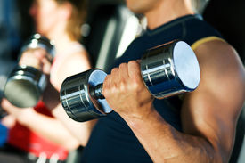 pic of weight-lifting  - Strong man exercising with dumbbells in a gym in the background a woman also lifting weights - JPG