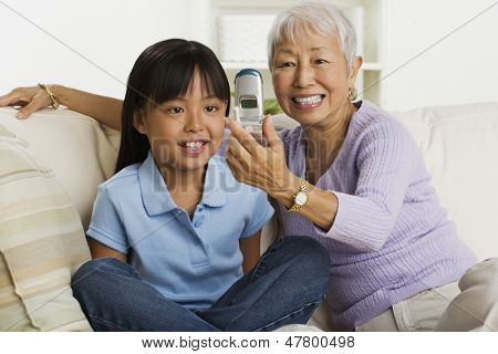 Grandmother and granddaughter looking at cell phone