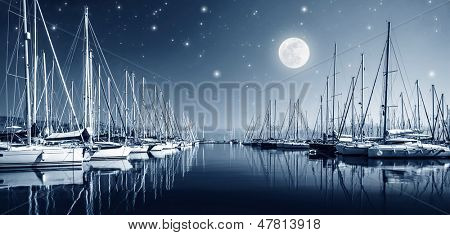 Beautiful landscape of yacht harbor at night, full moon, marina in bright moonlight, luxury water transport in nighttime, vacation concept