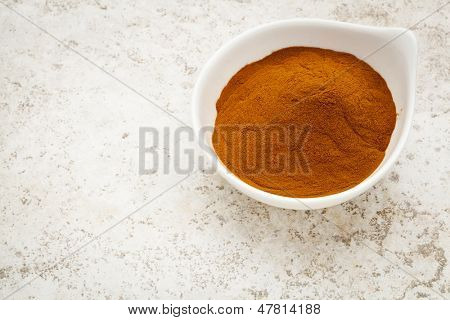 mangosteen fruit powder in a small bowl against a ceramic tile background