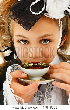 Beautiful tween girl in fantasy cosplay fashion sipping tea.