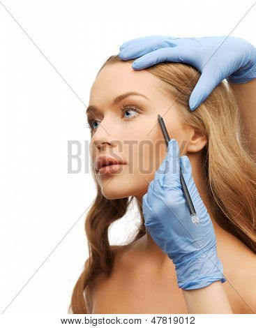 cosmetic surgery concept - woman face and beautician hands with pencil