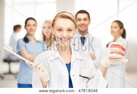 picture of attractive female doctor with toothbrush and jaws