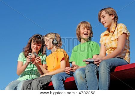 Group Of Kids Playing With Electronic Devices