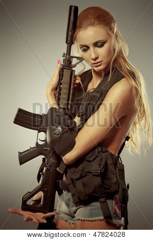 Portrait of a beautiful woman posing in a military style.