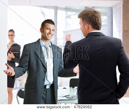 Young businessmen talking at meetingroom, smiling happy.