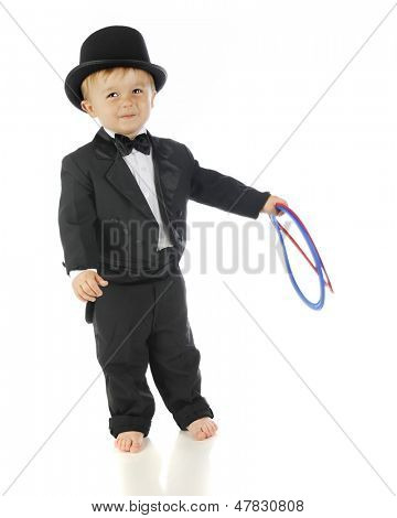 An adorable, barefoot toddler smiling in his tux and top hat.  He's holding two flexible rings.  On a white background.