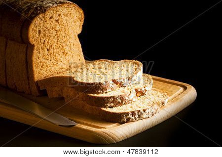 Sliced brown granary wholemeal loaf of bread on wooden chopping board