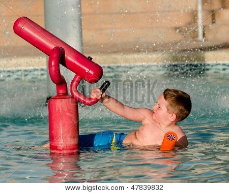 Child playing with water cannon at kiddie pool during summer