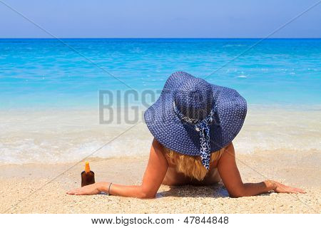 Woman laying on the beach in beach blue straw hat enjoying summer holidays looking at the ocean